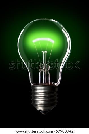 Light bulb turned on, black background. - stock photo