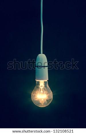 Light bulb turned on over black background - stock photo