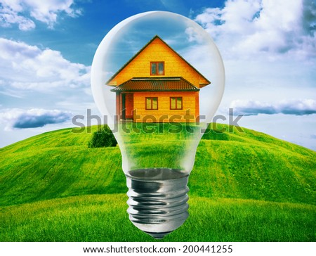 Light bulb with a house standing inside in green field. Eco technology and energy concept. - stock photo