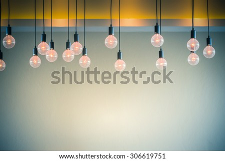 Light bulb with cement wall background - stock photo