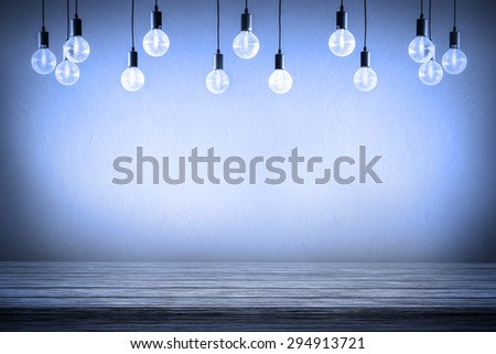 Light bulb with cement wall monochrome background,wood table - stock photo