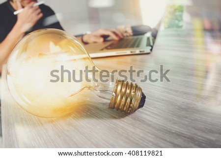light bulb with designer hand working with laptop computer and creative business strategy as concept - stock photo