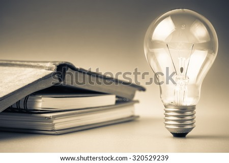 Light bulbs glowing with book - stock photo