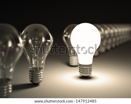 Light bulbs in a row with glowing one on black background. - stock photo