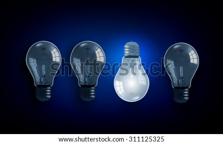 Light bulbs on dark background with one glowing