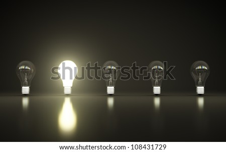 light bulbs stand in rows one glows - stock photo