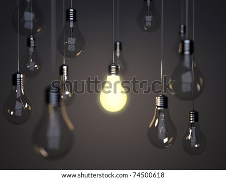 Light bulbs with one bright light bulb on a background a wall - stock photo