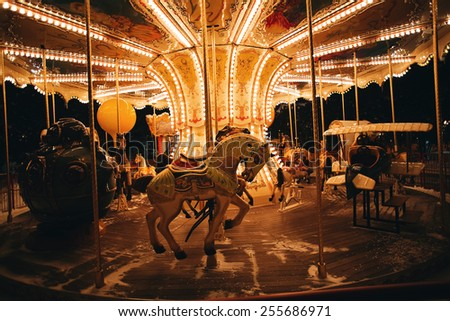 light carousel at night with horses in winter - stock photo