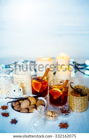 Light Christmas Decorations. Two Glasses with Mulled Wine, White Candles and Lantern, Toy Owl, Walnuts and Spices. Selective Focus, Shallow DOF. Space for Text. - stock photo