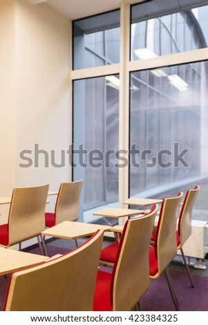 Light classroom with wood chairs, desks and big window