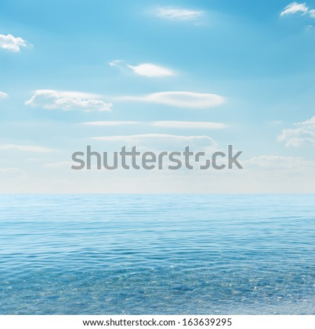 light clouds on sky over blue sea - stock photo