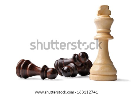 Light coloured wooden King chess piece standing upright surrounded by opposition pawns lying on their side in a game of strategy, on white
