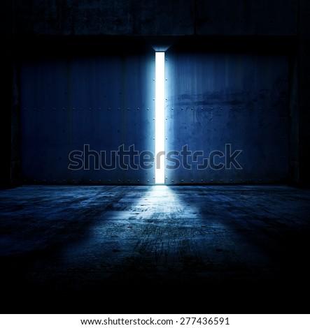Light coming in through opening of heavy steel doors .Large metal doors of an hanger like building opening and blue light coming in. - stock photo