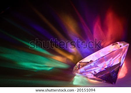 Light dispersed through a large crystal into rainbow colors - stock photo
