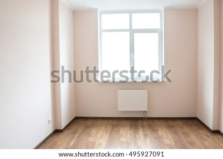 light empty room with big white isolated window and wooden floor