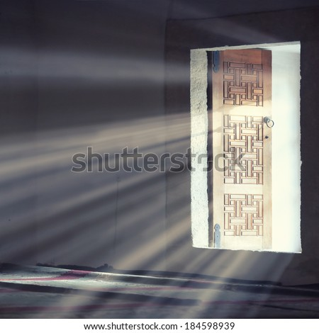Light entering through open door to a dark empty room.  - stock photo
