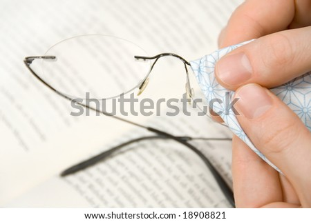 Light eyeglasses being cleaned in front of an out-of-focus book