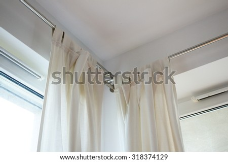 Light fabric curtains by an window - stock photo