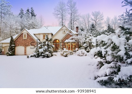 Light fades as night falls on a snowy suburban home - stock photo