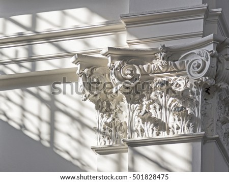 Light falls across a white column in a building
