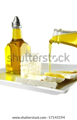 light feta cube with olive oil on white - stock photo