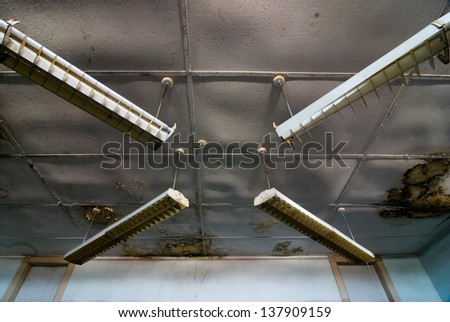 "light fixtures forming an ""x"" shape inside an abandoned school. - stock photo"