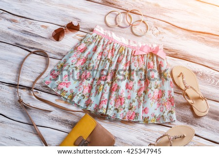 Light floral skirt and sandals. Sunglasses, bracelets and bag. Selection of accessories for girls. Bright colors of summer. - stock photo