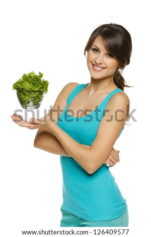 Light food concept. Smiling woman balancing lettuce leaves in transparent bowl, over white