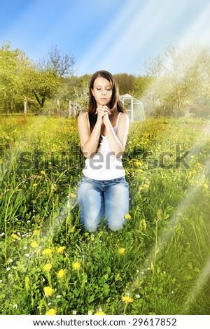 Light from heaven/girl pray in garden - stock photo