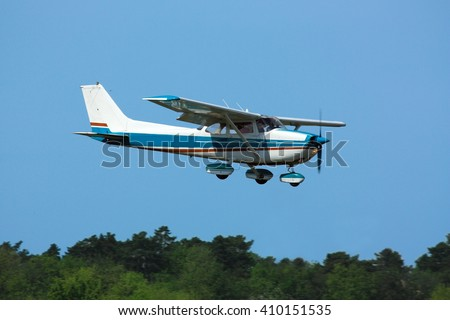 Light general aviation  plane on final over green trees - stock photo