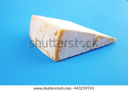 light gouda on blue plastic board - stock photo