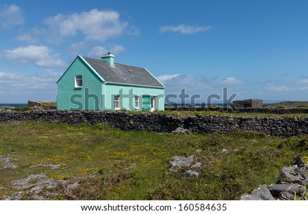 Light green painted small farmers agricultural home in south west Ireland or Eire. Stone built with slate roof and garden enclosed in solid stone walls - stock photo