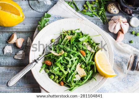 light green salad with arugula, cheese, almonds, lemon and olive oil, healthy food,top view - stock photo