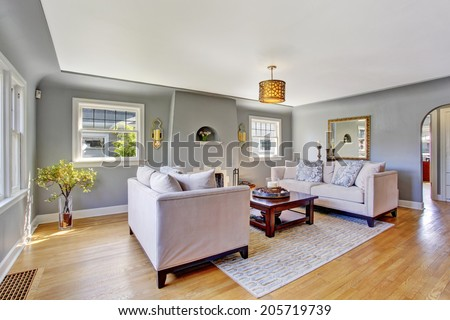 Light grey living rom with hardwood floor and rug. Furnished with white sofas and wooden coffee table - stock photo