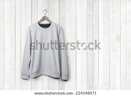 Light grey sweater on a white wood wall - stock photo