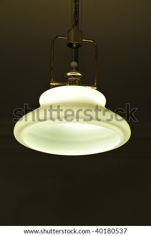 Light hanging from ceiling with the light on in a dark room - stock photo