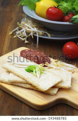 light healthy crisps with a bean sprouts and spring onion on a chopping board
