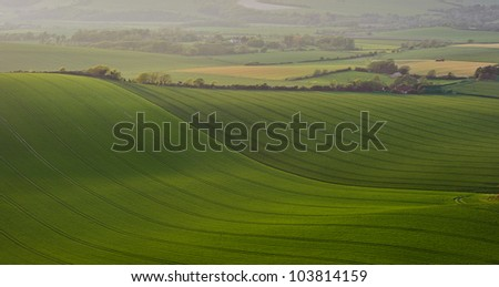 Light hits hills on rolling landscape in English countryside - stock photo