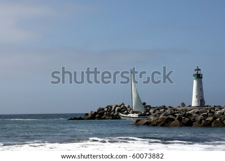 Light House and Boat Leaving Harbor - stock photo