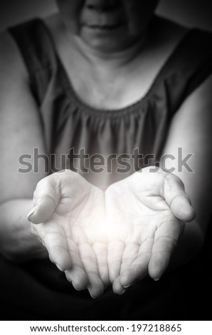 light in old woman hands - praying - stock photo