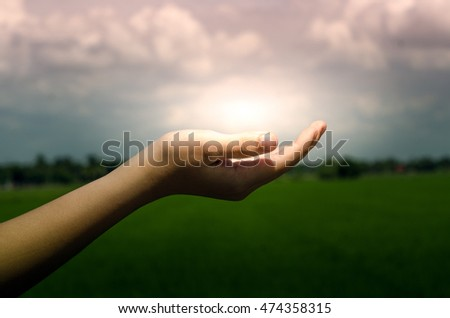 Light in the human hand on dark nature background.