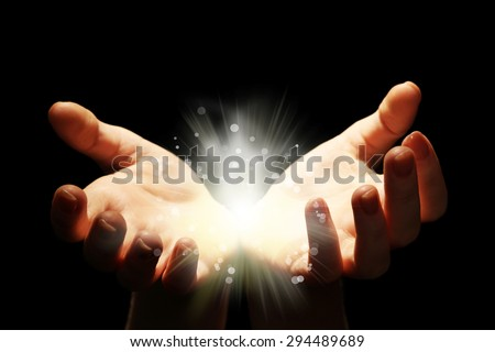 Light in the human hands in the dark - stock photo