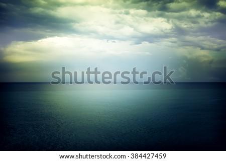 Light in the sky above the gloomy dark blue sea. Mediterranean nature. - stock photo