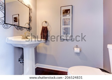Light lavender small bathroom interior with white toilet and washbasin stand