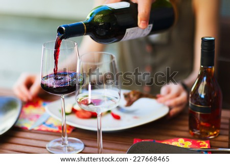 Light lunch with vegetable salad and red wine - stock photo