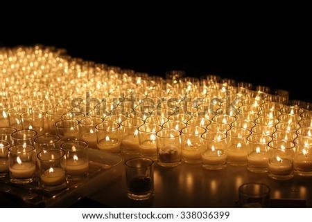 Light of candle in glasses illuminate on black background - stock photo