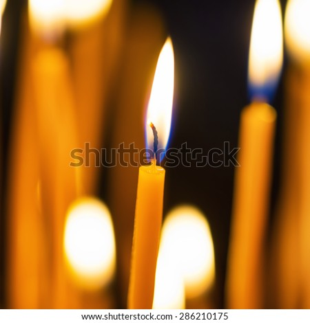 Light of candles in the church on the black background - stock photo