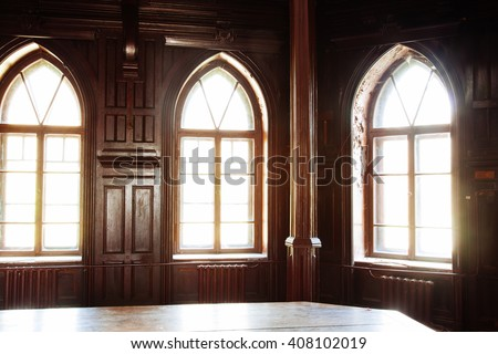 Light of the old wooden windows falls on the huge oak table in an abandoned building - stock photo