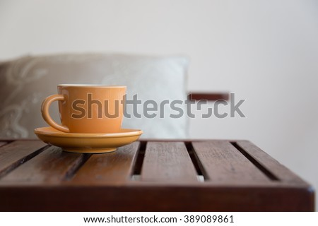 light orange coffee cup on wood table with copy space - stock photo