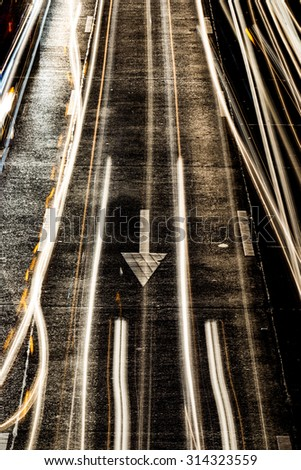 light painting on asphalt road by vehicle moving with arrow sign  - stock photo